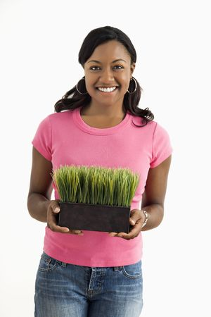 Portrait of smiling African American female standing holding patch of potted grass. Stock Photo - 3589404