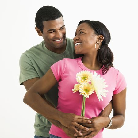 Portrait of smiling African American couple standing looking at each other.