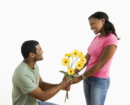 African American male giving pretty female a bouquet of yellow flowers.