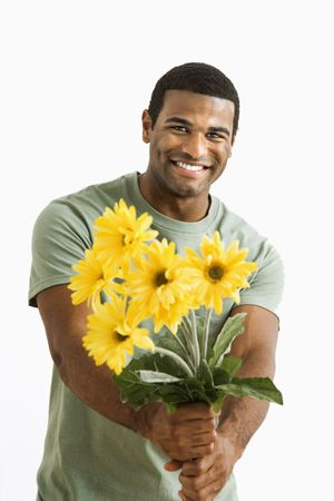 unseen: Smiling African American male holding out bouquet of yellow flowers to unseen person.