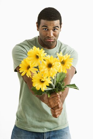 forgive: Pouting African American male holding out bouquet of yellow flowers to unseen person.