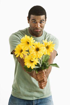 pardon: Tacaud African American hommes � la tenue bouquet de fleurs jaunes � la personne invisible. Banque d'images