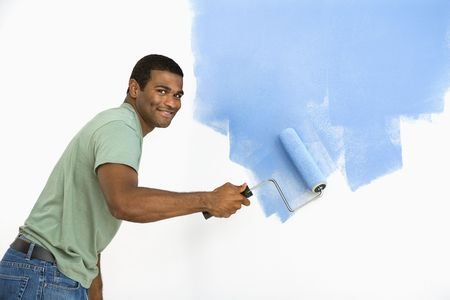 man painting: African American man painting wall blue smiling at viewer.