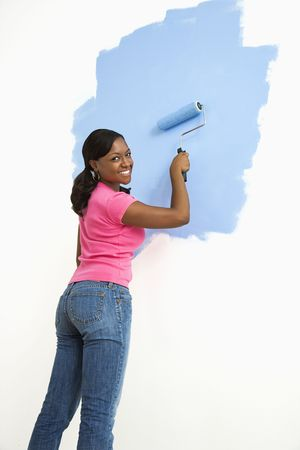 African American woman painting wall blue smiling at viewer. Stock Photo - 3589276