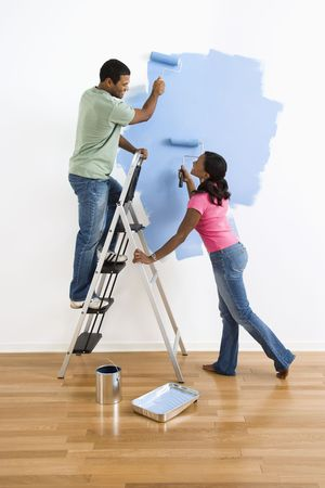 African American male and female couple painting wall blue and smiling at each other. photo