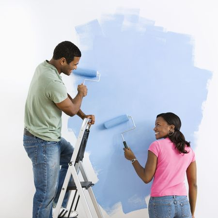 wall painting: African American male and female couple painting wall blue and smiling at each other. Stock Photo