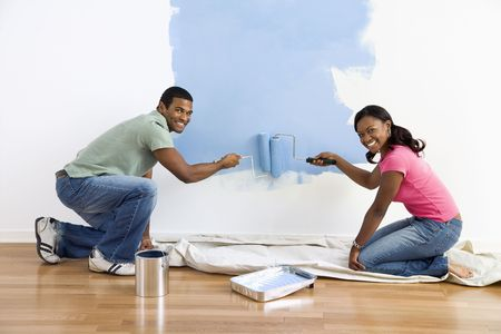 Smiling African American male and female couple painting wall blue. photo