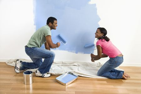 African American male and female couple painting wall blue. photo