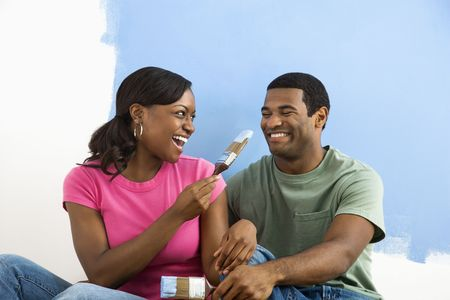 African American couple sitting and playing with paint brushes next to half-painted wall. photo