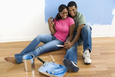 African American couple sitting together relaxing next to half-painted wall and painting supplies Stock Photo