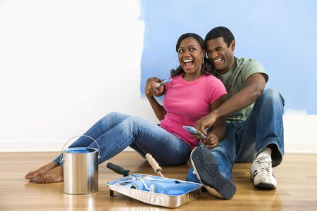 African American couple sitting together relaxing next to half-painted wall and painting supplies photo