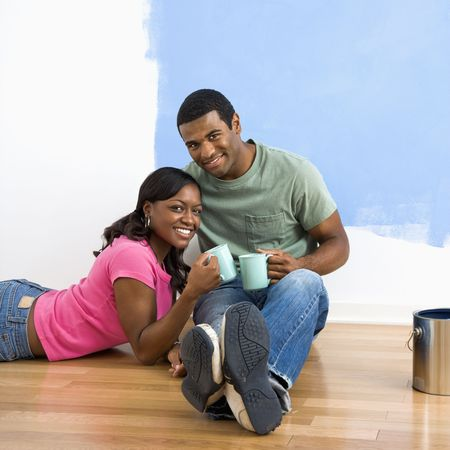 African American couple relaxing together with coffee next to half-painted wall. photo