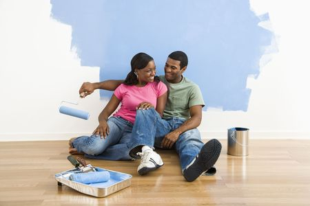 African American couple relaxing together next to half-painted wall and painting supplies. Stock Photo - 3589491