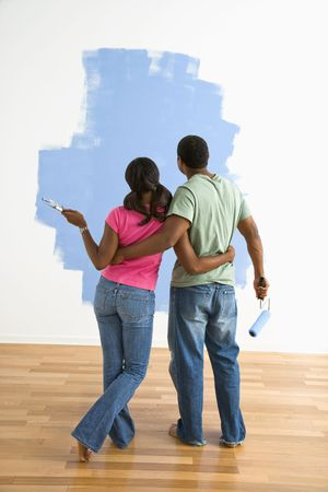 coppia in casa: African American matura in piedi cercando insieme a met� dipinte a muro.  Archivio Fotografico