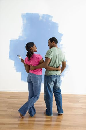 African American couple standing together next to half-painted wall discussing their work. photo