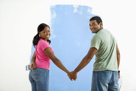 African American couple standing together in front of half-painted wall looking at viewer. Stock Photo - 3589470