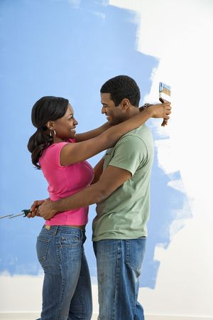 African American couple standing together hugging in front of half-painted wall. Stock Photo - 3589483
