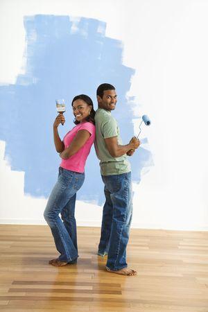 couple afro americain: African American couple � c�t� de demi-mur peint tels qu'ils sont dos � dos avec de la peinture ustensiles.