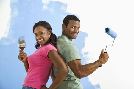 African American couple next to half-painted wall as they stand back to back with paint utensils.