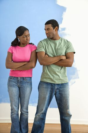 glaring: African American couple glaring at each other with anger next to half-painted wall. Stock Photo