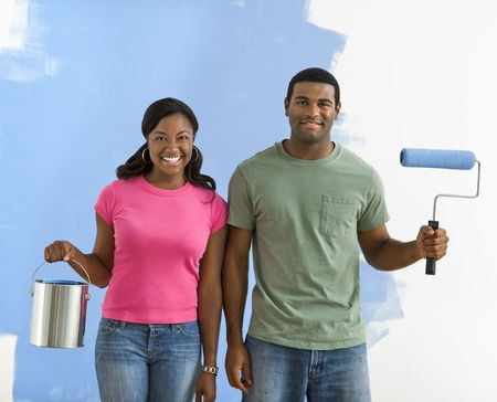 African American couple next to half-painted wall with paint supplies-American Gothic-style. photo