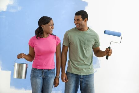 African American smiling couple next to half-painted wall with paint supplies. photo