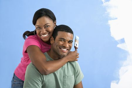 Portrait of African American male and female couple next to half-painted wall. Stock Photo - 3589469