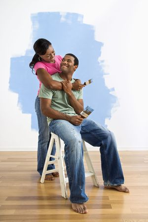 Portrait of African American couple next to half-painted wall. photo