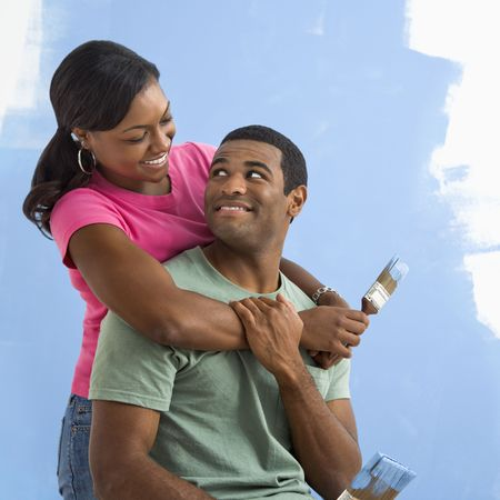 Portrait of African American male and female couple next to half-painted wall. photo