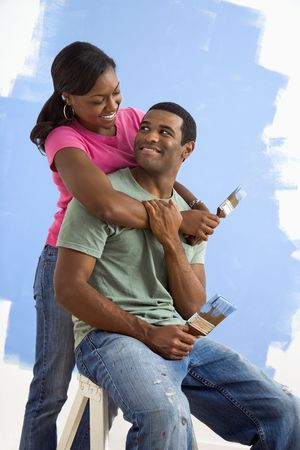 Portrait of African American male and female couple next to half-painted wall. Stock Photo