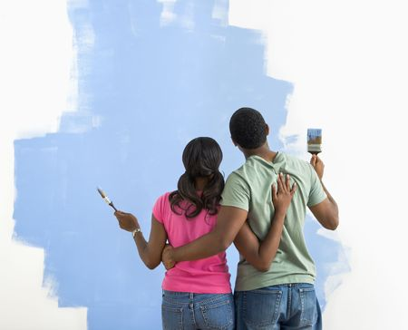 African American couple standing together looking at half-painted wall. photo