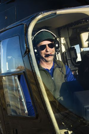 Portrait of helicopter pilot sitting in cockpit looking at viewer. photo