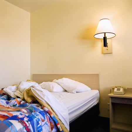 Interior shot of motel room with unmade bed and wall lamp. Stock Photo - 3584141