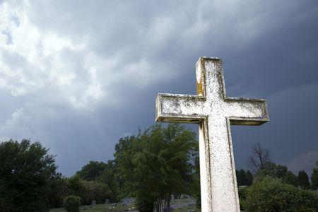 Cross in graveyard against stormy dark clouds in sky. photo