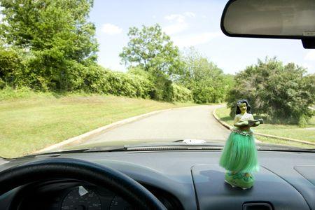 Hula girl on dashboard of car interior. Banco de Imagens