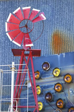 Broken red windmill against rusted blue corrugated metal building covered in taillights. photo