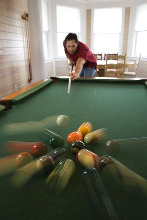 billiards room: Man shooting game of pool with balls scattering after hit.