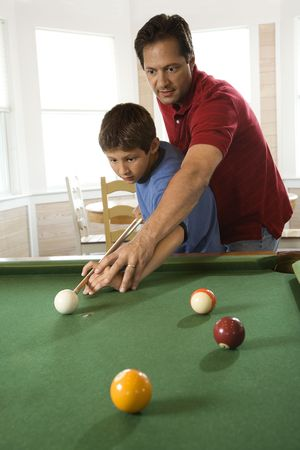 billiards room: Man shooting game of pool with young boy.  Vertically framed shot.