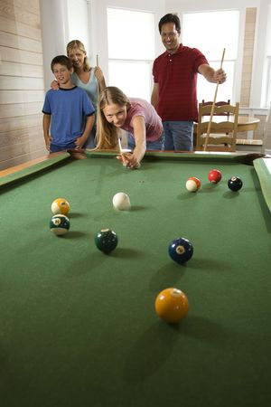 Girl playing pool with family in background. Vertically framed shot. photo