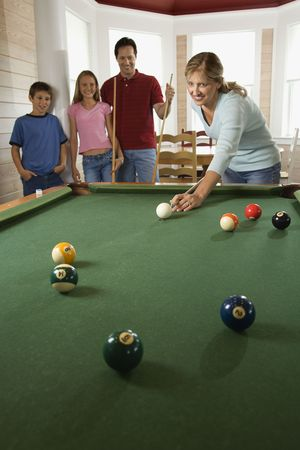 Woman playing pool with family in background. Vertically framed shot. photo