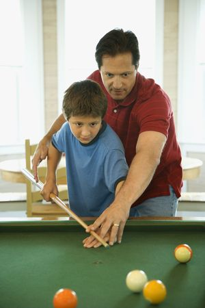 recreation: Man shooting game of pool with young boy.  Vertically framed shot.