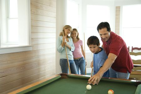 pool table: Man and boy shooting pool with woman and girl in background. Horizontally framed shot. Stock Photo