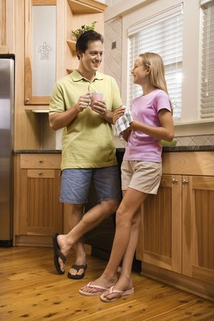 vertically: Man holding cup talking to young girl in kitchen.  Vertically framed shot. Stock Photo