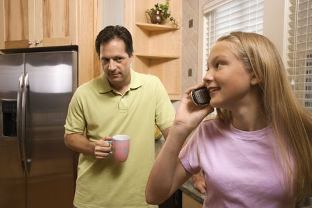 Father watching daughter talk on cell phone while in kitchen Stock Photo - 6235518