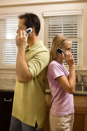 Father and daughter standing back to back talking on cell phones.  Vertically framed shot. Stock Photo - 6235542