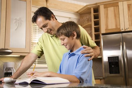 horizontally: Man helping young boy with homework.  Horizontally framed shot.