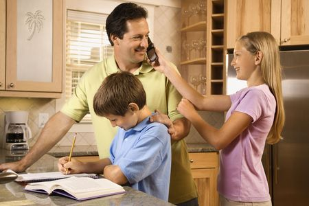 man phone: Daughter holding cell phone to fathers ear while young boy does homework. Stock Photo