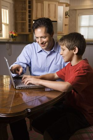 Father and son sitting at dining room table working on wireless laptop computer. photo
