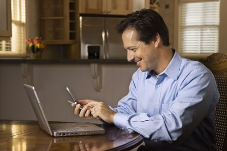 Man sitting at table smiling with cell phone and laptop. Horizontally framed shot.