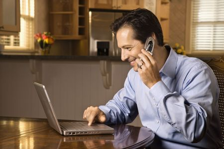 Man sitting at table smiling talking on cell phone and typing on laptop. Stock Photo - 6235512